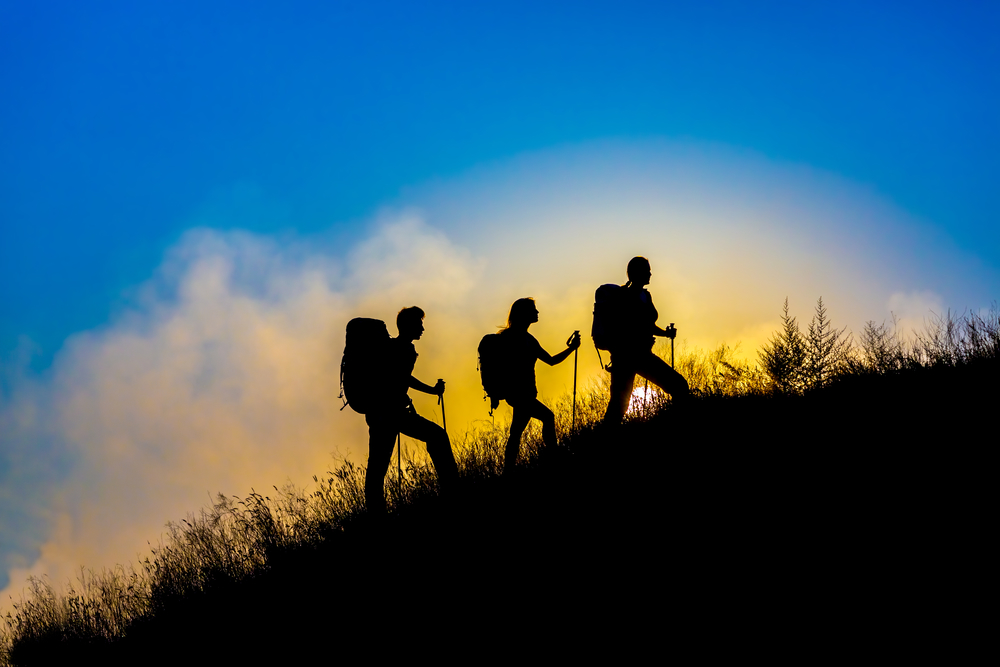3 people walking up a hill in walking boots and with walking equipment